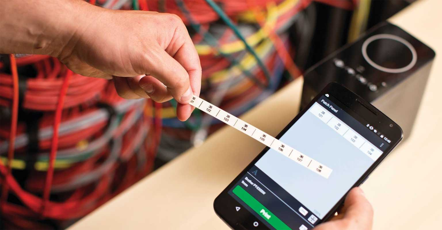 Cable label tool app on a smartphone with a printed Brother P-touch label