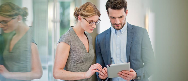 Nainen ja mies katsovat tabletin näyttöä