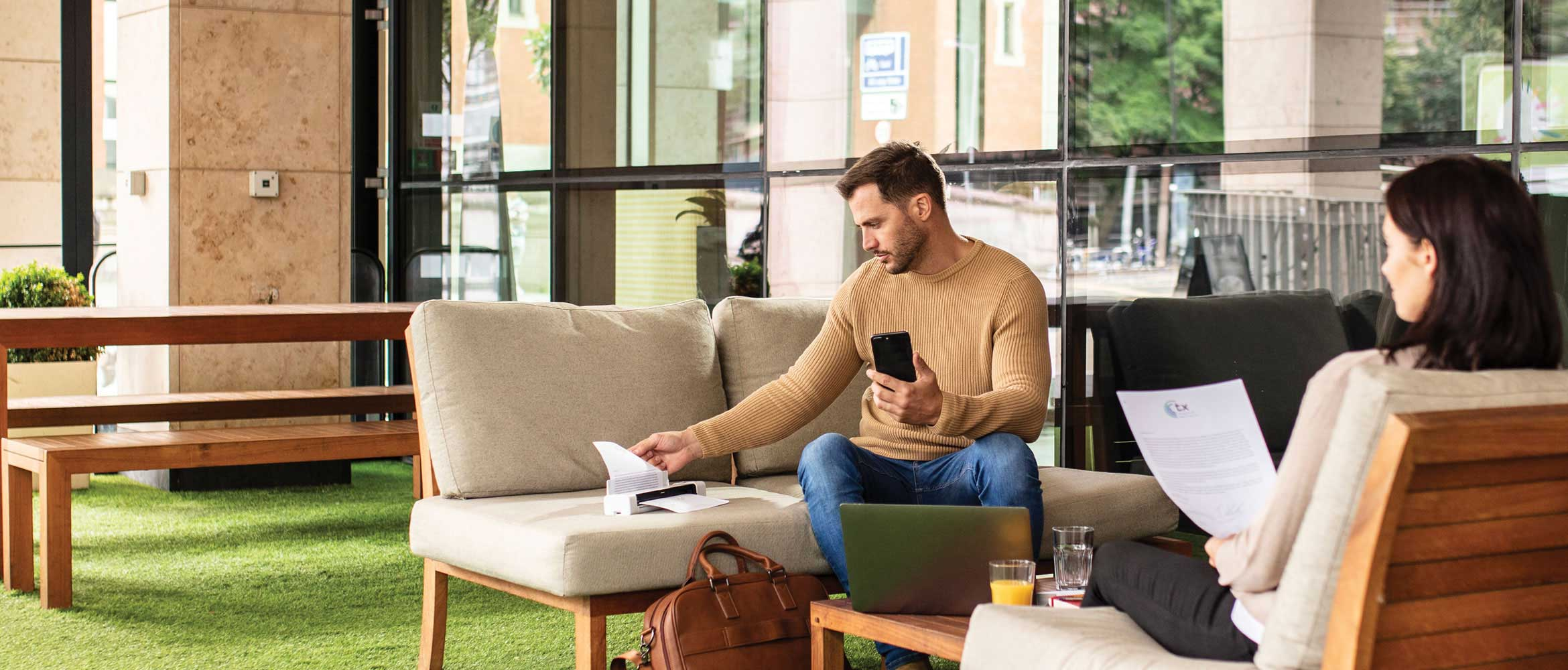 Man sat outdoors holding mobile phone using Brother DSmobile DS-940DW opposite woman holding A4 documemt, grass, wooden bench, plants