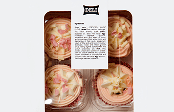 Pink and white cupcakes in a white and clear plastic box with a ingredient label